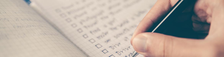 man d'homme écrivant une liste sur un carnet